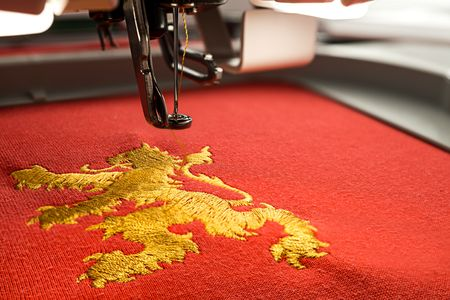 Close up picture of workspace embroidery machine and gold lion design on red fabric in th e hoop copy space on the right 写真素材