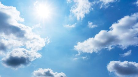 The sun is shining on the blue sky and cumulus clouds nature background