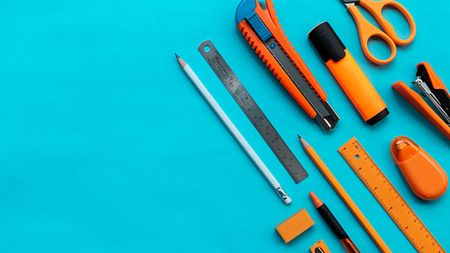 Group of orange stationery on blue color paper, flat lay picture. Imagens