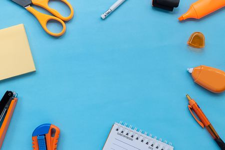 Flat lay picture of orange stationery and office supplies on blue color paper background. close up