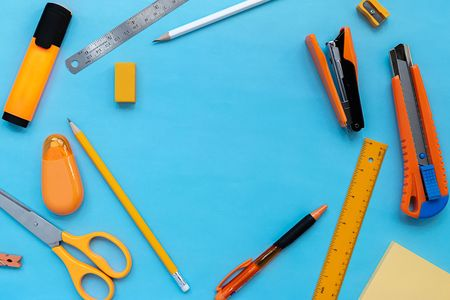 Flay lay picture of orange stationery office supplies on blue color paper.