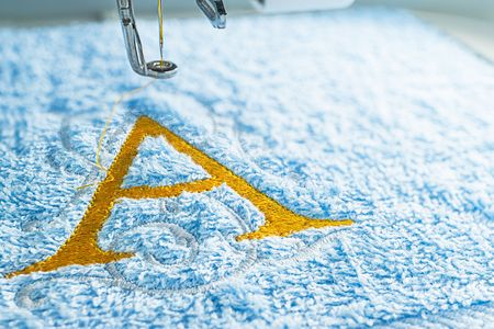 Close up picture of embroidery design yellow alphabet on towel embroider by machine, copy space on the right side.