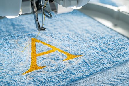Close up picture of embroidery machine and yellow monogram A alphabet design on towel