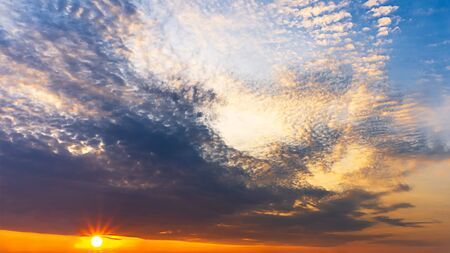 Nature background of twilight cloudy sky and sun shinning. Banco de Imagens