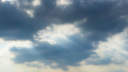 Cloudy blue sky and silver lining light from the sun behide the clouds background