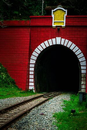 Entrance of old railway tunnel in mountain forest Banco de Imagens