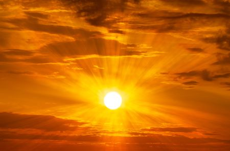 The brightly yellow sun is shining on the orange sky and clouds at golden hour time sunrise or sunset scene nature background Banco de Imagens