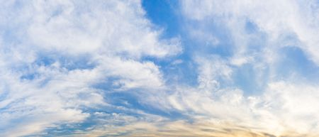 Panorama morning blue sky and white silky smooth clouds and sun light nature calm background Banco de Imagens