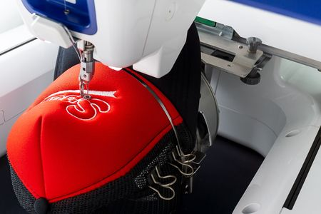 Working white embroidery machine embroidering logo on red and black sport cap, close up picture Фото со стока