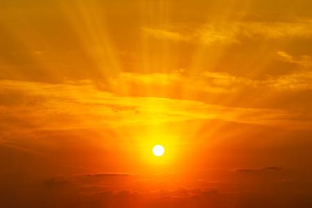 El sol brillando en el cielo naranja y las nubes en el fondo de la naturaleza de la hora dorada Foto de archivo
