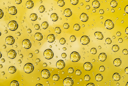 Water drops and lemon fruit in reflection on glass surface  look like bubble texture abstract yellow background