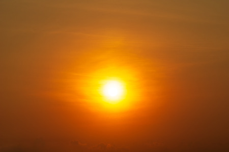The bright yellow sun shining on golden hour  orange sky and cloud nature background