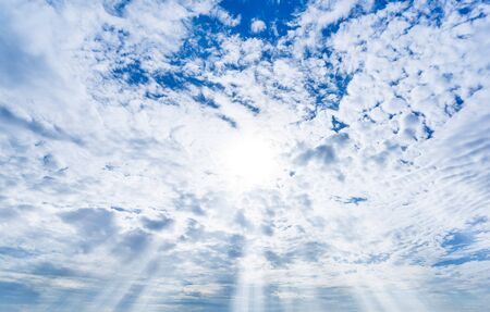 Blue sky with full white fluffy cloud and sun shining cloudy day nature background