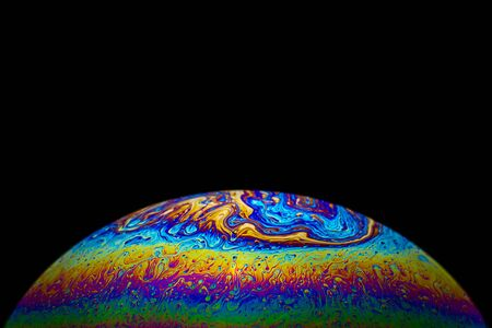 Close up soap bubble on black background psychedelic color look like small liquid planet in deep space