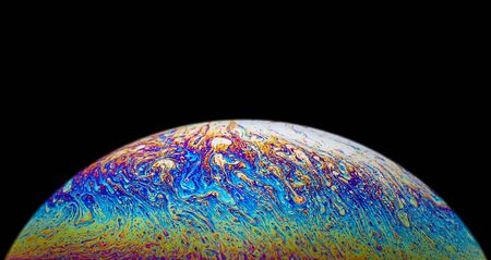 Close up picture of soap bubble on black background look like psychedelic liquid color planet in deep space Reklamní fotografie