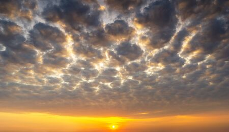 Fluffy altocumulus clouds and sun with golden light, nature background sunrise or sunset scenic.