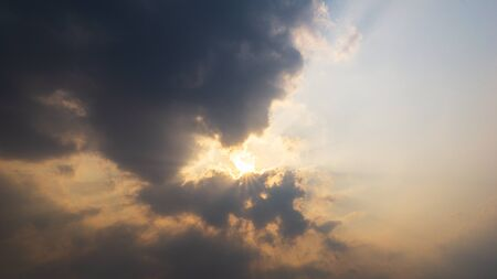 The sun shining behind cloudy sky nature background