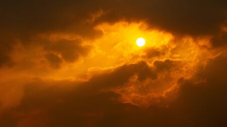 Orange dramatic cloudy sky and bright sun nature background copy space