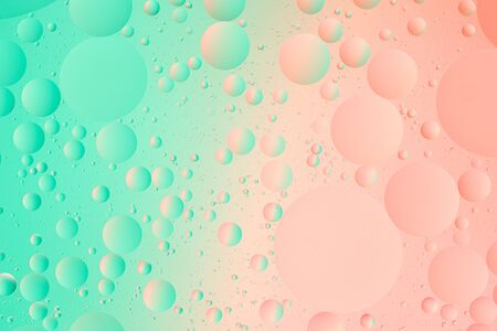 Abstract green and pink gradient color macro background of oil bubbles on water