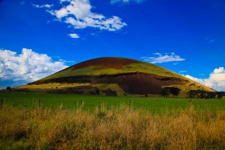 scoria: Mount Elephant volcanic cone, extinct volcano in grass farm land on sunny vivid blue sky day  Stock Photo