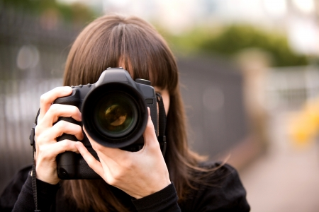 photographing: Woman taking a photo in the city during the day with bokeh background
