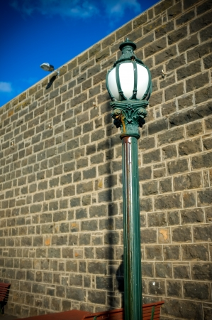 Old style street lamp post with blue stone wall and bright blue sky photo