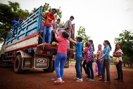 SIEM REAP, CAMBODIA - CIRCA JUNE 2012: Students hopping on a truck used as school bus June 2012 in SIEM REAP, CAMBODIA.