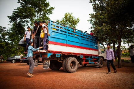 SIEM REAP, CAMBODIA - CIRCA JUNE 2012: Students hopping on a truck used as school bus June 2012 in SIEM REAP, CAMBODIA. Stock Photo - 16070103