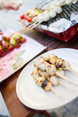 shishkabab: Thai style BBQ chicken balls on skewer grilling on a plate in outdoor cooking area