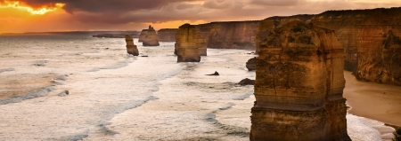 Golden sunset at 12 Apostles rock formation in Victoria, Australia  Dusk sun setting behind the backlit apostles with sea fog rolling in to the cliff face  photo
