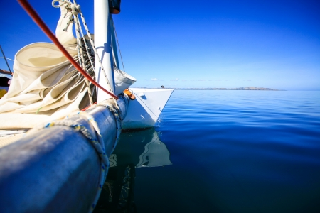 View of the bow of a sailing boat in calm blue sea with red rope riggings and white mast  photo