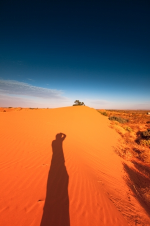 sandhills: Photographer shadow on Red outback ripple sand dune desert with blue sky. Stock Photo