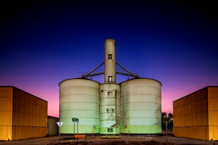 Old grain storage rustic silo during a stunning pink purple blue dusk sunset in country Victoria of Australia photo
