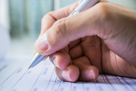 filling out: Hand with pen over application form on blure water glass background
