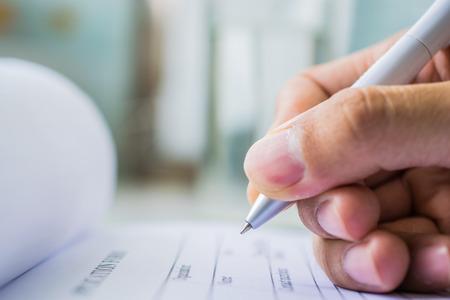 Hand met pen over aanmeldingsformulier op blure waterglas achtergrond