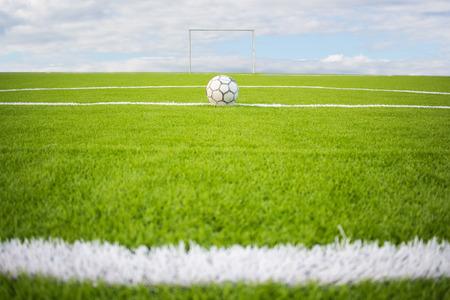 pasto sintetico: Artificial turf football field green on sky background