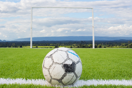 Soccer ball on Artificial turf football field green white grid with sky backgound