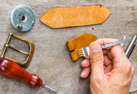 Leather and craft tools on wooden background