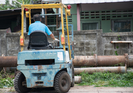 Man Working On The Forklift. Metal pipe on the forklift. Stock Photo