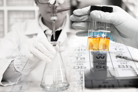 titration: Scientist is doing the experiment, the titration of the reagent in the flask, tube in scientist hand