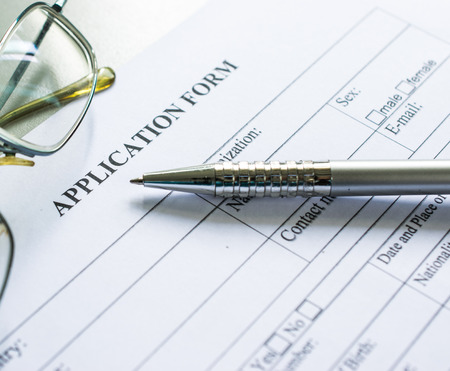 Close up of a job application form on desk with pen and glasses Stock Photo