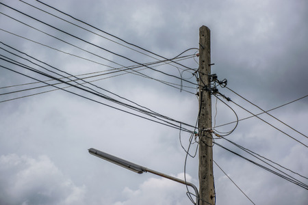 Electricity pole and street light complicated wiring With Dark Storm Clouds Stock Photo