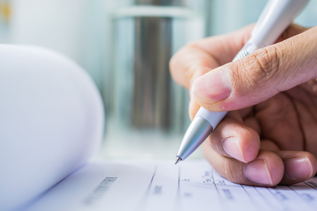 Hand met pen over aanvraagformulier op blure waterglas achtergrond