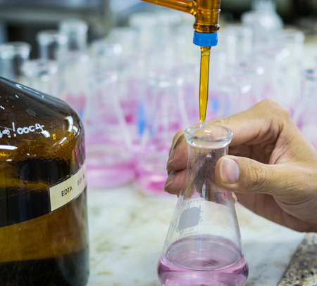 Scientist fill chemical into erlenmeyer flask