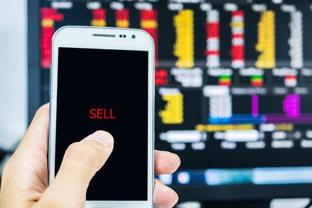 Effectenbeurshandelaar die telefoon bekijken geen marktmonitor