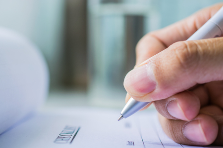 Hand with pen over checklist from on blure water glass background Stock Photo