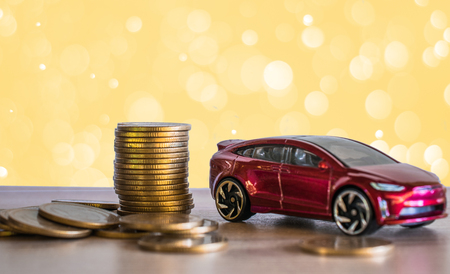 Loan Finance Concepts, toy car and coins on golden light bokeh background