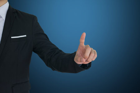 Businessman touch on virtual screen on blue background.