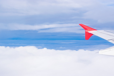 Aircraft Wing of airplane flying on cloud and bluesky background Stock Photo