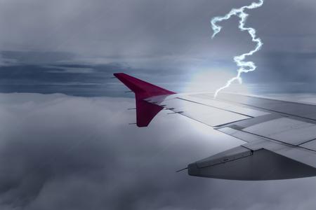 Lightening strikes Aircraft Wing of airplane on dark sky Stock Photo